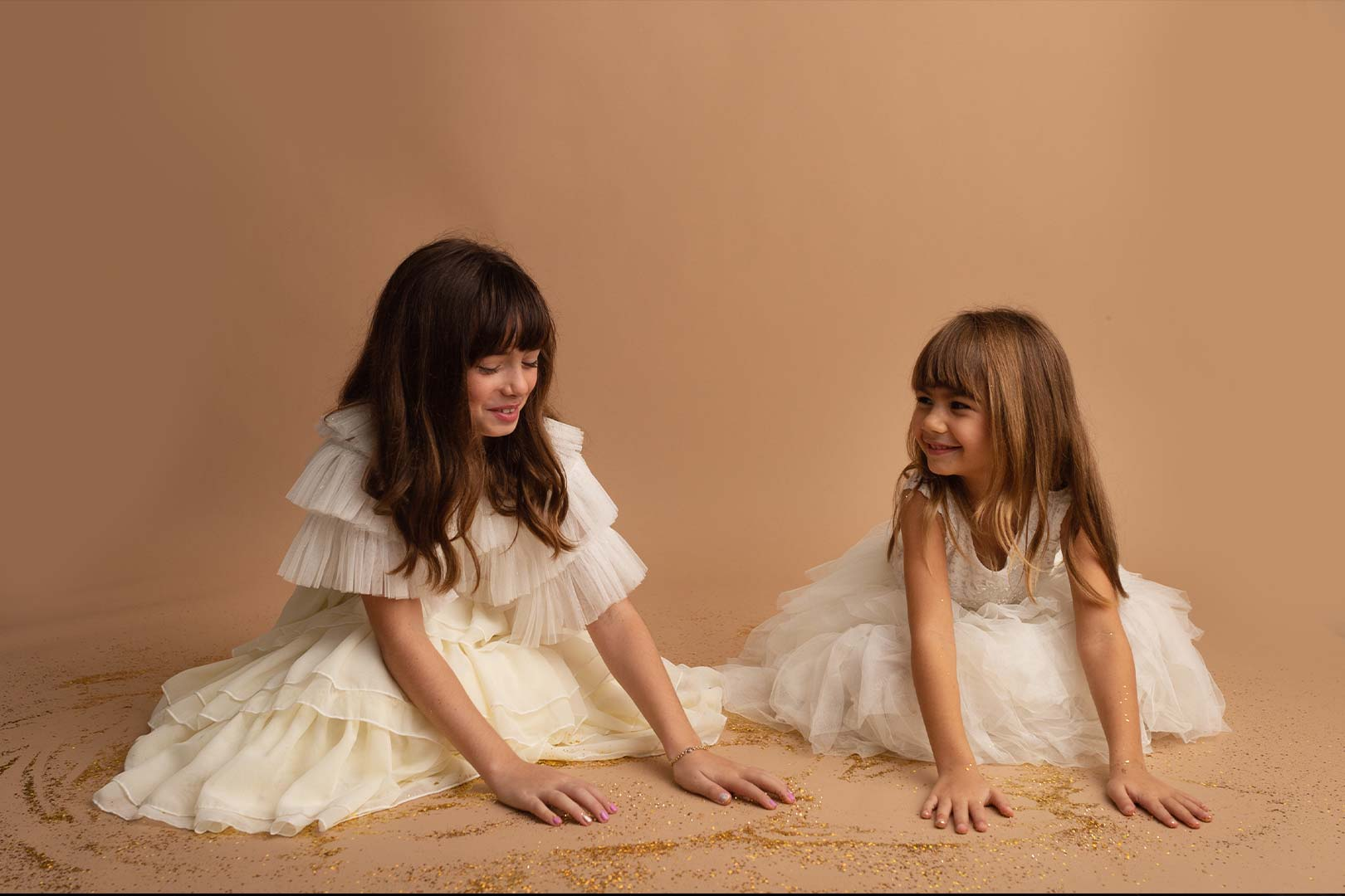 two girls in white dress playing on the floor